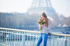 有束的女孩在埃佛尔铁塔附近的红色郁金香 图库摄影