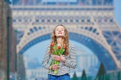 有束的女孩在埃佛尔铁塔附近的红色郁金香 库存图片