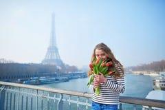有束的女孩在埃佛尔铁塔附近的红色郁金香 免版税库存图片