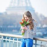有束的女孩在埃佛尔铁塔附近的红色郁金香 免版税图库摄影