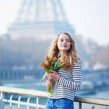 有束的女孩在埃佛尔铁塔附近的红色郁金香 免版税库存照片