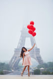 有束的妇女在埃佛尔铁塔附近的红色气球在巴黎 库存图片