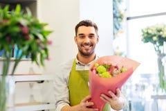 有束的微笑的卖花人人在花店 免版税图库摄影