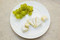 有束的板材绿色葡萄和乳酪片 免版税库存照片