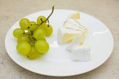有束的白色板材绿色葡萄和乳酪片 免版税库存照片