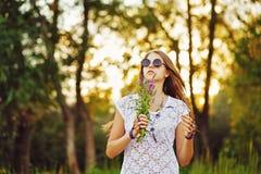 有束野花和太阳镜的Boho女孩在森林里 库存图片