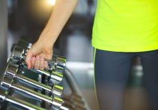 有杠铃的健身妇女在健身房背景 免版税库存照片