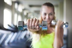 有杠铃的少妇在健身房背景 库存图片