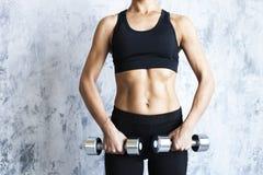 有杠铃的肌肉妇女在织地不很细墙壁上 免版税库存照片