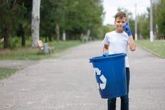 有条理的十几岁的男孩拿着一个蓝色回收站和说在被弄脏的自然本底的电话里 免版税库存图片