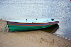 有条纹的小船在水后的岸 免版税库存图片