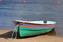 有条纹的绿色小船在岸 免版税库存图片
