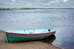 有条纹的绿色小船在水后的岸 免版税库存照片