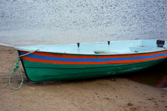 有条纹的绿色小船在水后的岸 图库摄影