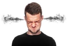 有来自他的耳朵的烟的恼怒的人 免版税库存图片