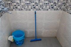 有杯子和刮水器的蓝色桶在卫生间里 免版税库存图片