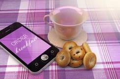 有杯子和油炸圈饼的手机 库存图片
