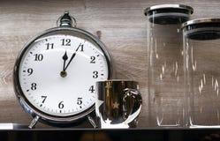 有杯子和玻璃瓶子的闹钟在木背景 免版税图库摄影