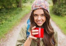 有杯子和背包远足的微笑的少妇 免版税图库摄影