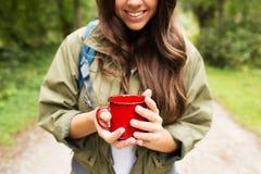 有杯子和背包远足的微笑的少妇 图库摄影