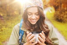 有杯子和背包远足的微笑的少妇 库存图片