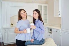 有杯子的两个女朋友在他们的手上在一次会议上在屋子里 库存照片