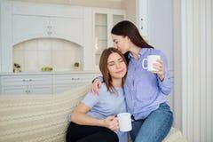 有杯子的两个女朋友在他们的手上在一次会议上在屋子里 免版税库存照片
