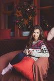有杯子的妇女热的饮料坐沙发由装饰的圣诞树 免版税库存照片