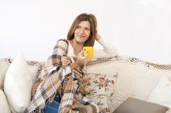 有杯子的微笑的女孩在沙发 库存图片