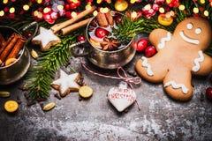 有杯子的微笑的姜饼人被仔细考虑的酒、圣诞节装饰和假日曲奇饼和香料在黑暗的土气背景wi 免版税库存图片