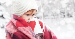 有杯子的愉快的儿童女孩热的饮料在冷的冬天户外 免版税库存图片