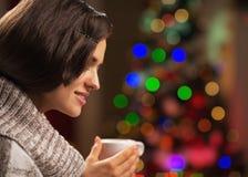 有杯子的愉快的妇女在圣诞树前面的热巧克力 免版税库存图片