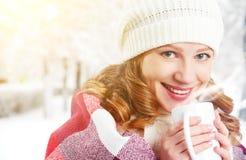 有杯子的愉快的妇女热的饮料在冷的冬天户外 免版税库存照片