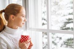 有杯子的愉快的少妇在冬天窗口圣诞节的热的茶 免版税库存照片