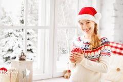 有杯子的愉快的少妇在冬天窗口圣诞节的热的茶 库存图片