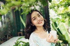 有杯子的愉快的年轻亚裔妇女在手上喝咖啡standi的 免版税库存图片