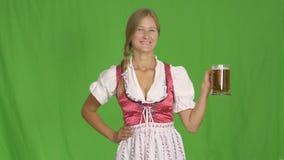有杯子的慕尼黑啤酒节女孩在绿色的啤酒 股票录像