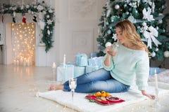 有杯子的白肤金发的少妇在圣诞灯和圣诞树前面的热巧克力 免版税图库摄影