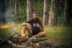 有杯子的行家远足者放松在篝火在森林里 图库摄影