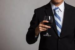 有杯的亚裔商人身体红葡萄酒 库存照片