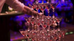 有杯的侍者手在金字塔的香槟在党的承办酒席期间 夹子 杯金字塔香槟 股票录像