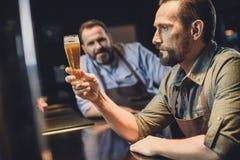 有杯的啤酒厂工作者啤酒 图库摄影