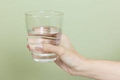有杯的妇女手水 免版税库存图片