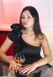 有杯的妇女桃子白兰地酒 库存图片