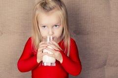 有杯的小逗人喜爱的女孩牛奶 免版税库存图片