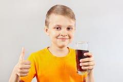 有杯的小滑稽的男孩新鲜的可乐 免版税库存图片