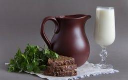有杯的布朗水罐牛奶 免版税图库摄影