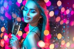 有杯的性感的式样女孩在迪斯科聚会,在假日发光的蓝色背景的饮用的香槟的香槟 免版税图库摄影