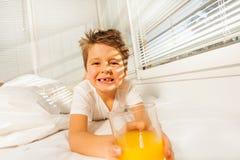 有杯的愉快的男孩汁液在晴朗的早晨 图库摄影
