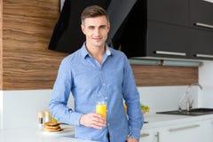 有杯的愉快的英俊的人新鲜的橙汁 免版税图库摄影